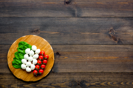 Italian flag made of mozzarella cheese, cherry tomatoes, green basil on wooden cutting board on dark wooden background top view space for text