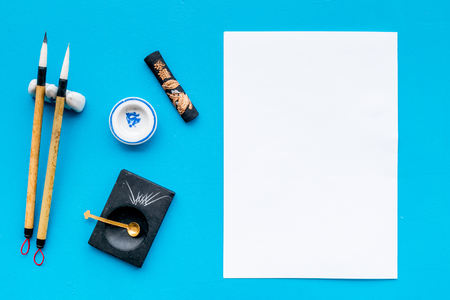 Lesson of calligraphy concept. White blank sheet for lettering near writing accessories on blue background top view. Stock fotó - 112657749