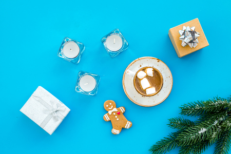 New Year or Christmas concept with hot drink. Cocoa with marshmallow, gift box, gingerbread man, candles, fir branches on blue background top view Stock Photo