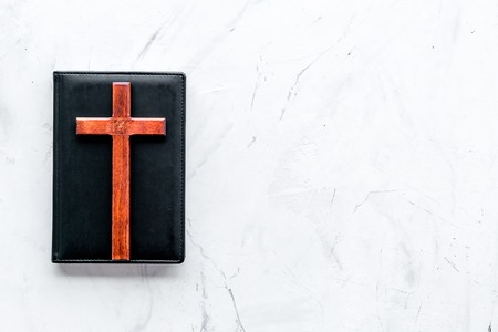 Farewell ceremony, funeral concept. Wooden cross on Bible on white background top view. Reklamní fotografie