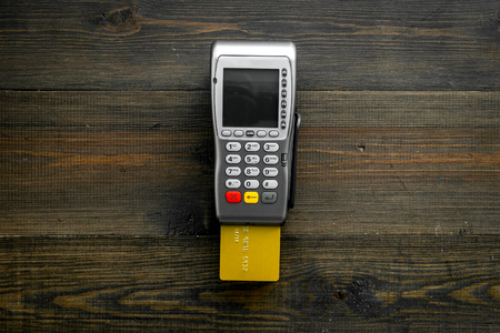 Pay by card. Bank card inserted in payment terminal on dark wooden background top view. Reklamní fotografie