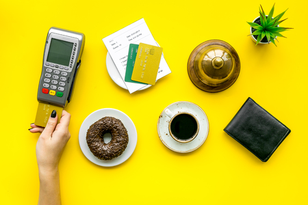 Pay the bill by payment terminal. Womans hand insert bank card in payment terminal near bill, service bell, coffee and donuts on yellow background top view.