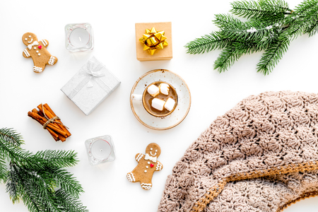 Romantic winter composition with hot drink. New Year or Christmas Eve. Cocoa with marshmallow, gift box, gingerbread man, wool blanket, fir branches on white background top view Stock Photo