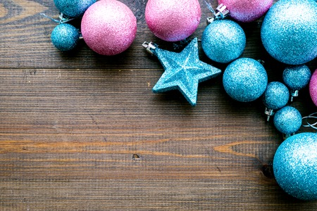 Toys for New Year tree 2019 background. Blue and pink balls and stars on dark wooden background top view. Stock Photo
