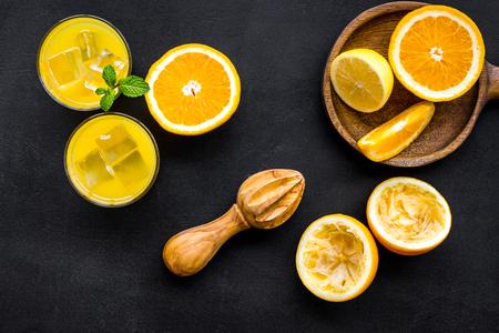 Squeeze fresh oranges with juicer. Orange juice in glass near half cut oranges on black background top view
