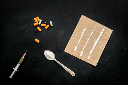 Take drugs, drugs addiction concept. White powder like heroine or cocaine, drug tracks pills, spoon, syringe on black background top view.