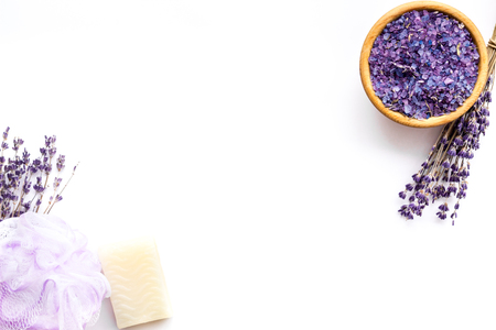 Spa set with lavender spa salt. Purple spa salt near dry lavender branches and washcloth on white background top view copy space