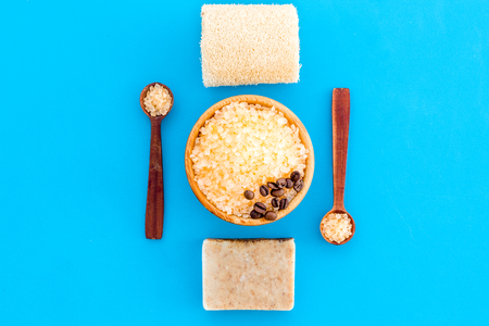 Aromatherapy and spa concept. Spa salt with coffee scent near soap, spa oil and loofah on blue background top view.