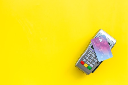 Paypass technology. Bank card lays on payment terminal on yellow background top view.