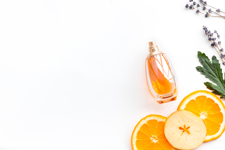 Bottle  of perfume near apple, orange, lavender on white background