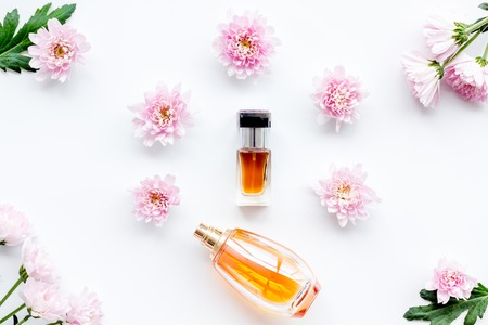 Bottle of perfume near delicate pink flowers on white background Stock Photo