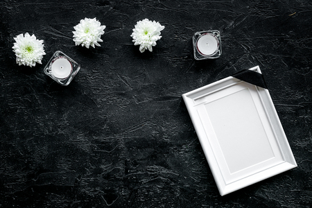 Death concept. Photo frame, mockup with black ribbon near flowers, candles on black background