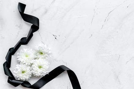 Weiße Blume in der Nähe von schwarzem Band auf weißem Steinhintergrund