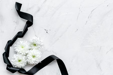 White flower near black ribbon on white stone background