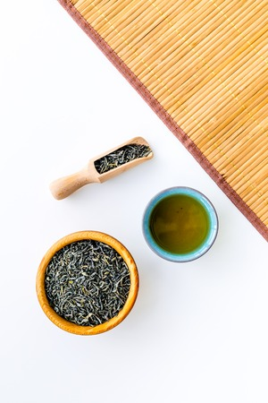 Dry tea leaves in bowl and wooden scoop near cup of tea on white background and bamboo table mat