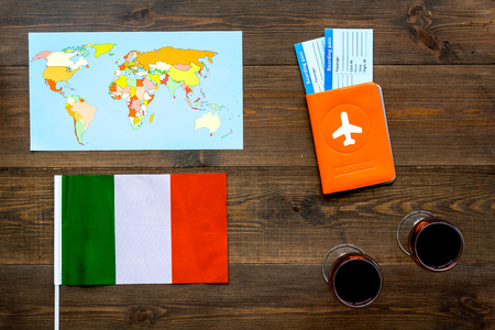 Passport and tickets near italian flag, glass of red wine, map of the world on dark wooden background