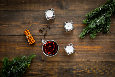 Winter beverage for New Year or Christmas Eve with Mulled wine near fir branches, candles, cinnamon on dark wooden background