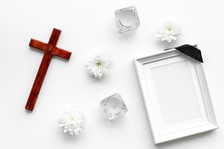Funeral concept. Mockup of portrait of the deceased. Frame with black ribbon near flowers, candles and cross on white background Zdjęcie Seryjne