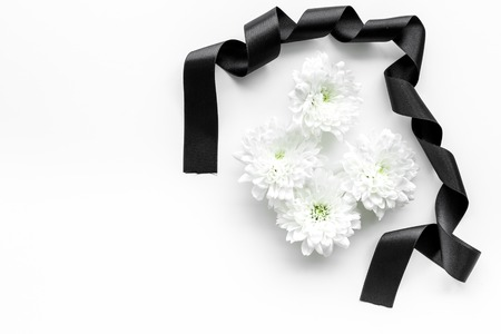 Funeral symbols concept. White flower near black ribbon on white background