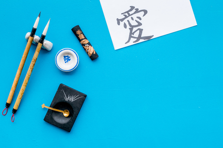 Chinese or japanese calligraphy concept. Hieroglyph love near traditional written accessories on blue background top view. Reklamní fotografie