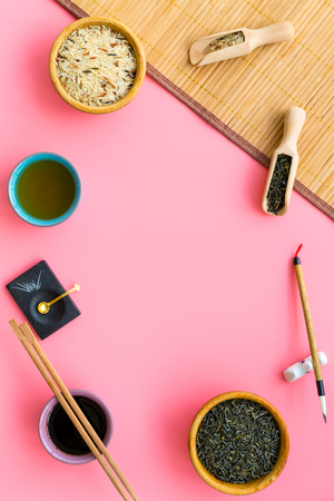 Chinese traditional symbols concept. Tea, rice, hieroglyph love, bamboo table mat, chopsticks, soy sause on pink background top view frame.
