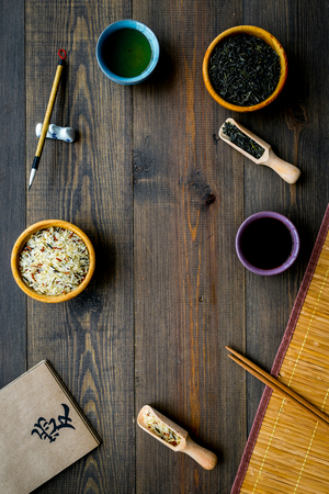 Chinese traditional symbols concept. Tea, rice, hieroglyph love, bamboo table mat, chopsticks, soy sause on dark wooden background top view frame. Stockfoto - 112801810