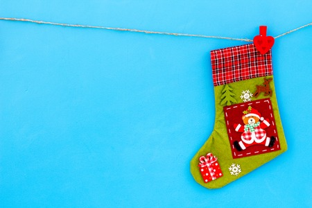 Decorative Christmas socks. Empty socks for gift hanging off a thread on blue background top view.