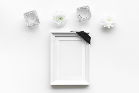 Photo frame, mockup with black ribbon near flowers, candles on white background top view. Stok Fotoğraf
