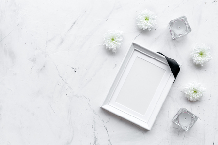 Photo frame, mockup with black ribbon near flowers, candles on white background top view.