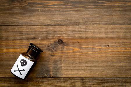 Botella con calavera y tibias cruzadas sobre fondo de madera oscura.