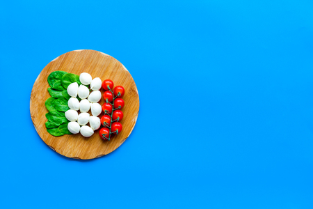 Italian flag made of mozzarella cheese, cherry tomatoes, green basil on wooden cutting board on blue background Stock Photo
