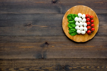 Italian flag made of mozzarella cheese, cherry tomatoes, green basil on wooden cutting board on wooden background