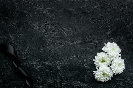Witte bloem in de buurt van zwart lint op zwarte achtergrond bovenaanzicht.