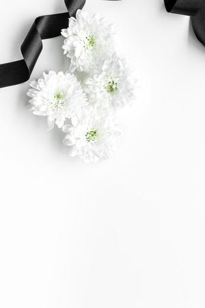 White flower near black ribbon on white background top view.