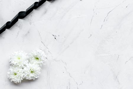 White flower near black ribbon on white stone background top view. Zdjęcie Seryjne - 112799615