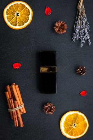 Bottle of perfume near orange, lavender, cinnamon, pine cones on black background top view.