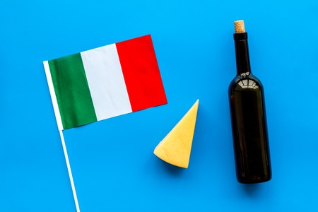 Italian flag, cheese parmesan and bottle of red wine on blue background top view.