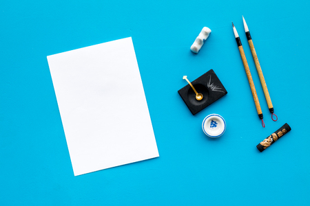 Lesson of calligraphy concept. White blank sheet for lettering near writing accessories on blue background top view.