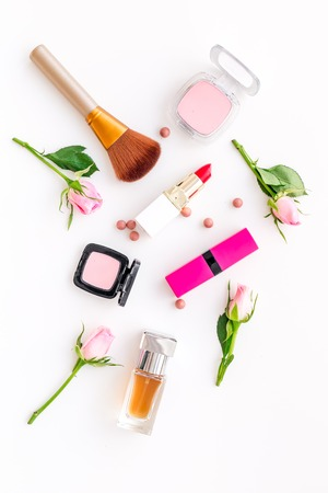 Lipstick, bulk, eyeshadow, perfume, brushes and rose flowers on white background top view. 免版税图像
