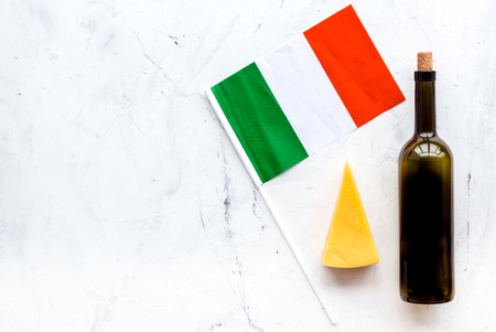 Italian flag, cheese parmesan and bottle of red wine on white background top view.