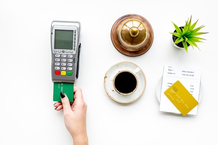 Womans hand insert bank card in payment terminal near bill, service bell, coffee on white stone background top view.