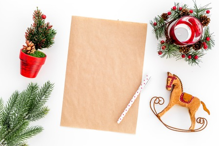 Blank letter wishlist for Santa Claus near fir branches, toy horse on white background top view.