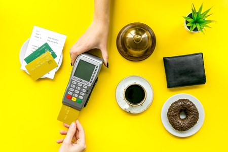 Woman's hand offer payment terminal. Woman's hand insert bank card in payment terminal near bill, service bell, coffee and donut on yellow  background top view.