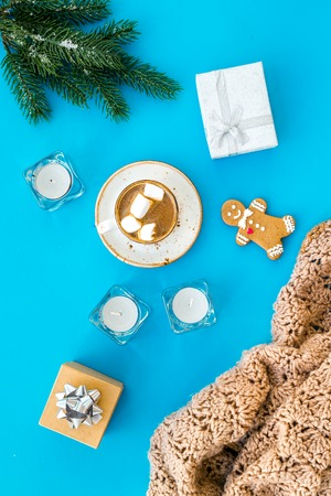 Cocoa with marshmallow, gift box, gingerbread man, wool blanket, fir branches on blue background top view.