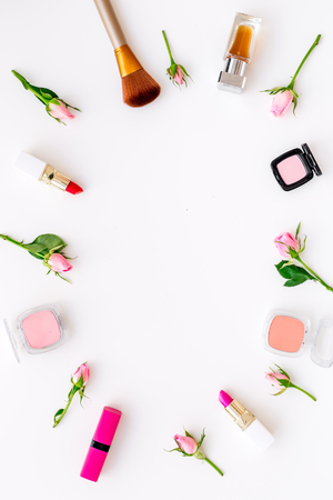 Lipstick, bulk, eyeshadow and small rose flowers on white background
