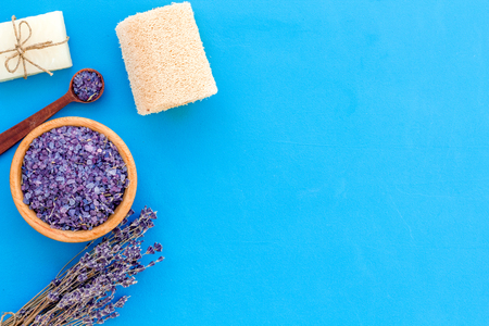 Purple spa salt near dry lavender branches and washcloth on blue background top view.