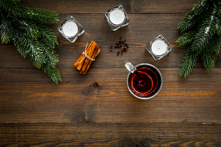 Mulled wine near fir branches, candles, cinnamon on dark wooden background Stock Photo