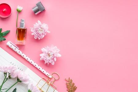 Perfume cerca del cuaderno para productos lácteos entre flores en la vista superior de fondo rosa. Foto de archivo