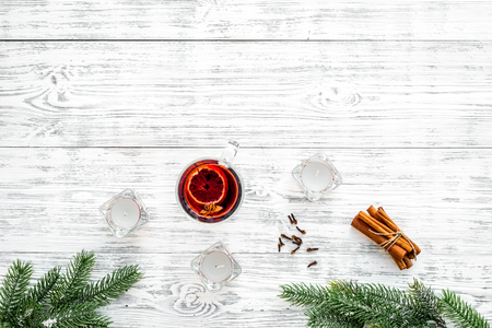 Mulled wine near fir branches, candles, cinnamon on white wooden background