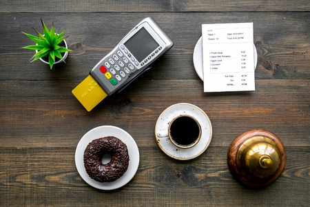 Electronic payments. Pay the bill by card concept. Bank card inserted in payment terminal near bill, service bell, coffee and donut on dark wooden background top view